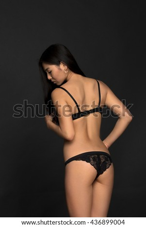 Picture of fashion asian model in black lingerie demonstrating her gorgeous back in studio. Brunette lady looking down.