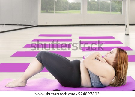 Picture of fat woman doing sit up exercise on the mat, shot at fitness center