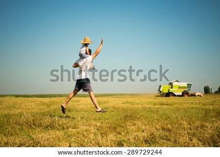 Picture of father on field walking fast riding his son on shoulders wearing straw hat waving hand at combined harvester over blue sky background copyspace - stock photo