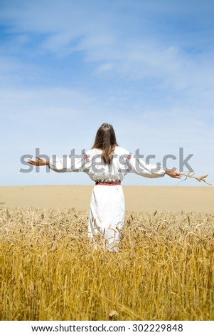 Picture of female in traditional dress standing hands up to sky relaxing in wheat field on summer day background outdoors