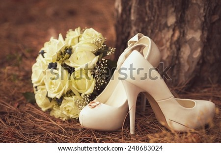 Picture of female white wedding shoes with a bouquet On green grass - stock photo