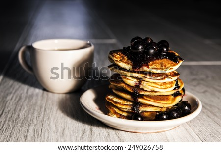 Picture of few pancakes with blackberries and cup of tea on wooden background - stock photo