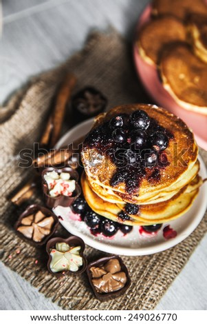 Picture of few pancakes with blackberries and sugar on wooden background - stock photo