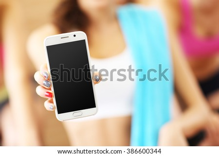 Picture of fit woman holding smartphone in gym - stock photo