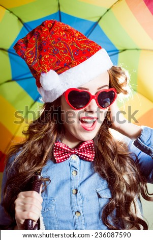 picture of funny hipster beautiful girl in heart shape sunglasses wearing Christmas Santa hat over rainbow umbrella background happy smiling and looking at camera - stock photo