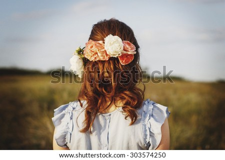 Picture of girl standing back with flowers in head - stock photo