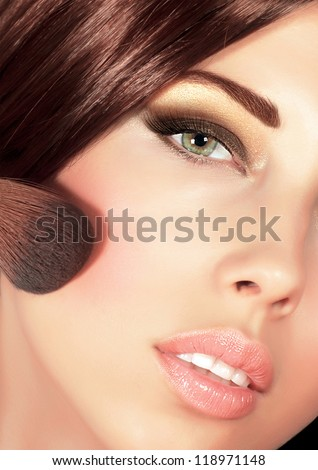 Picture of gorgeous woman with brown silky hair doing evening makeover, sexy look, smoky eyes, fashionable makeup, stylish visage, professional cosmetics brush and tassel, luxury beauty salon - stock photo