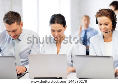 picture of group of people working with laptops in office - stock photo