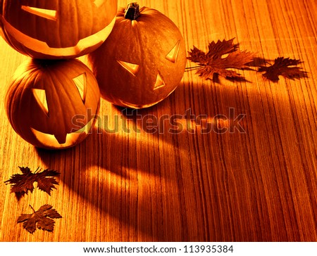 Picture of halloween glowing pumpkins border, three orange carved pumpkins and old dry leaves on wooden background, scary holiday shadow, traditional halloween decoration, jack-o-lantern - stock photo