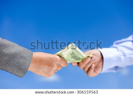 Picture of hands giving and receiving dollar bills. Side view in horizontal format over a blue sky sunny outdoors background.