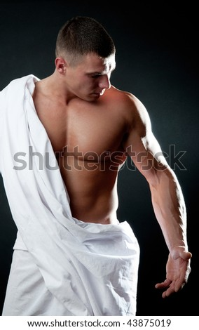 Picture of handsome athlete looking on his arm