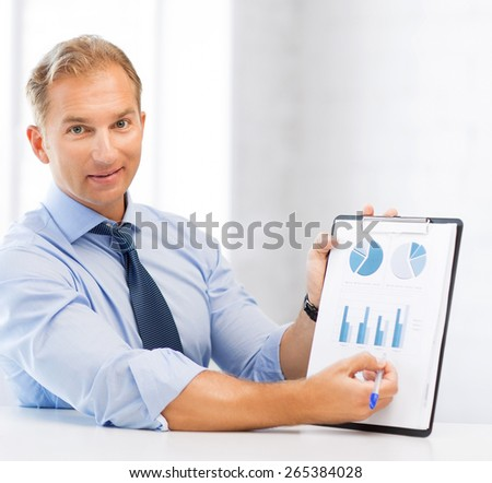 picture of handsome businessman showing graphs and charts - stock photo