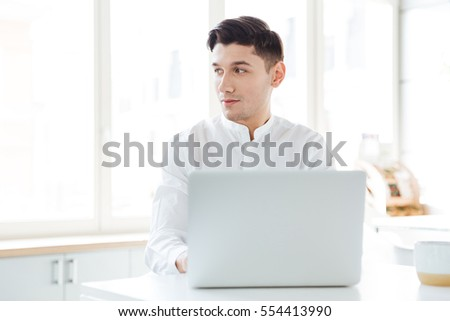 Picture of handsome man dressed in white shirt using laptop computer. Coworking. Looking aside.