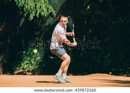 Picture of handsome young man on tennis court. Man playing tennis.  - stock photo