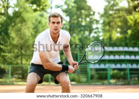 Picture of handsome young man on tennis court. Man playing tennis. Man is ready to hit tennis ball. Beautiful forest area as background - stock photo