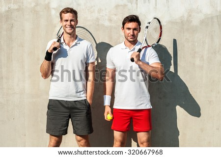 Picture of handsome young men on tennis court. Men cheerfully smiling, looking at camera and holding tennis racquets - stock photo