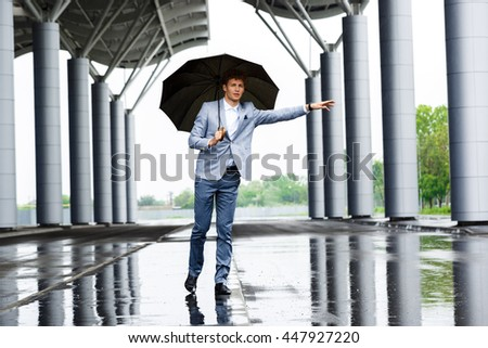 Picture of handsome young redhaired businessman catching the car and holding umbrella looking at camera