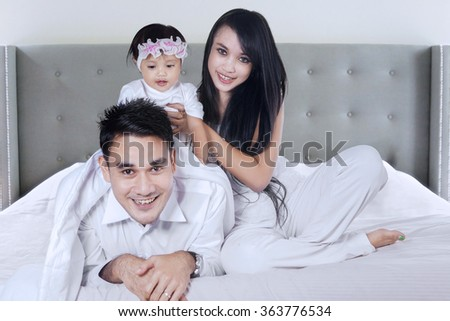Picture of happy asian family having fun together and smiling at the camera in the bedroom - stock photo
