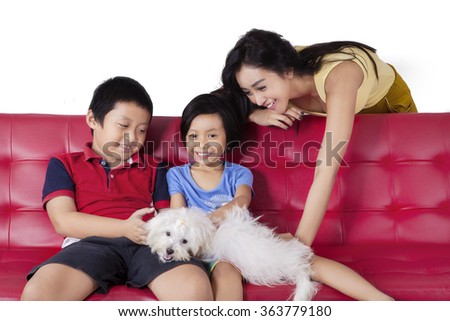Picture of happy children sitting on the sofa while playing their puppy with mom, shot at home - stock photo