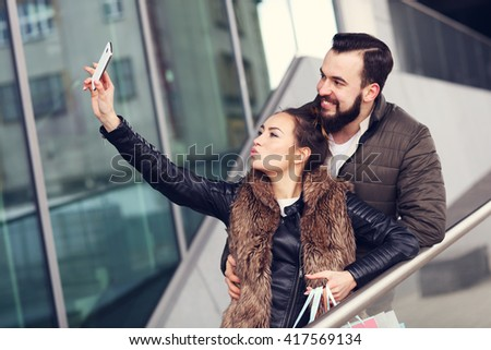 Picture of happy couple huggingand taking selfie while shopping