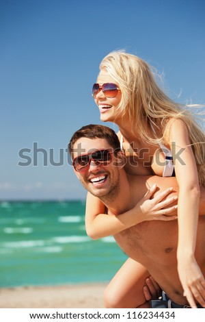 picture of happy couple in sunglasses on the beach (focus on man). - stock photo