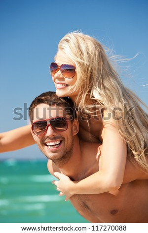 picture of happy couple in sunglasses on the beach (focus on man) - stock photo