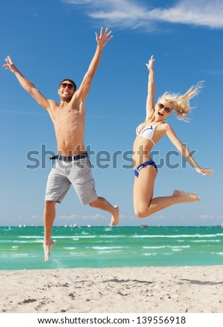 picture of happy couple jumping on the beach - stock photo