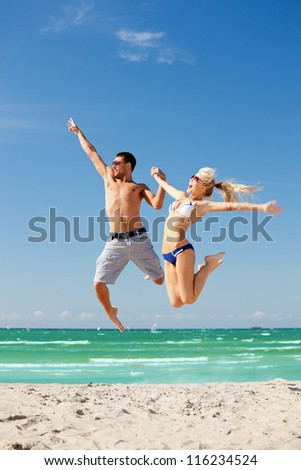 picture of happy couple jumping on the beach (focus on man). - stock photo