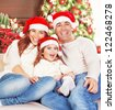 Picture of happy family sitting on sofa and wearing red Santa Claus hats, cheerful parents with daughter having fun at Christmas eve, little girl with mother and father celebrate New Year - stock photo