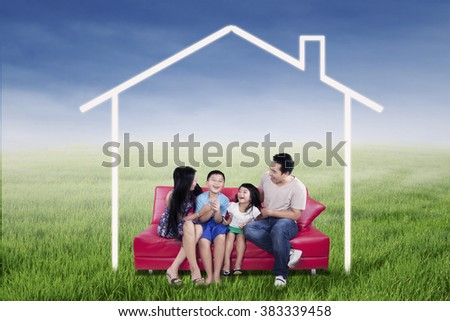 Picture of happy family sitting on the sofa while having fun together under a dream house on the meadow