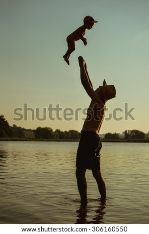 Picture of happy father and child having fun on the summer beach over water outdoors background   - stock photo