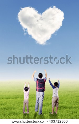Picture of happy father and his children raise hands together on the meadow under cloud shaped heart symbol