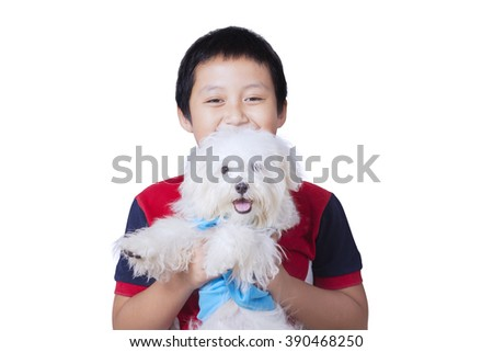 Picture of happy little boy holding a maltese dog in the studio, isolated on white background - stock photo