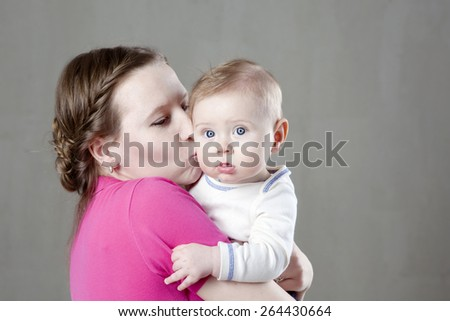 Picture of happy mother kissing her adorable baby - stock photo