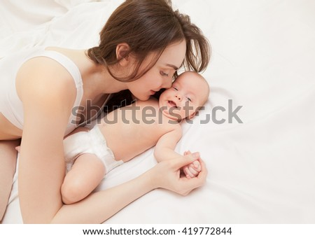 Picture of happy mother kissing her adorable baby lying on bed - stock photo