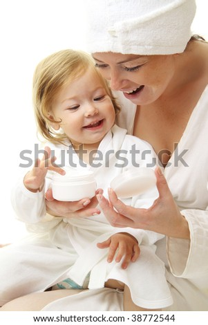 picture of happy mother with baby holding cosmetic cream - stock photo