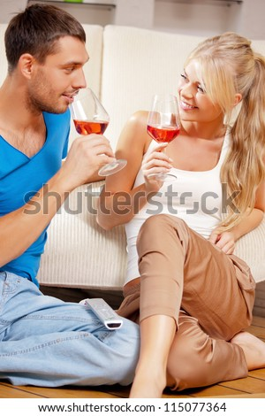 picture of happy romantic couple drinking wine (focus on woman) - stock photo