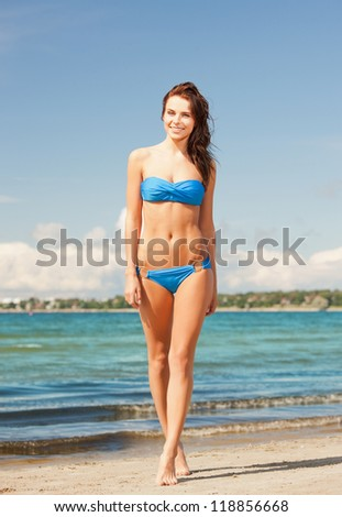 picture of happy smiling woman walking on the beach. - stock photo
