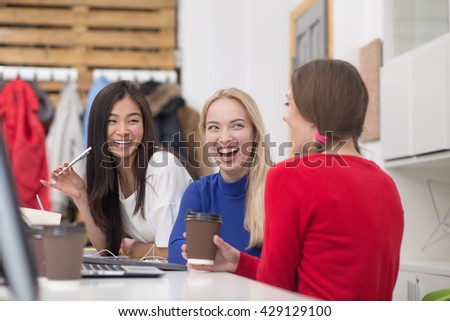 Picture of happy students smiling and laughing in library. Beautiful ladies drinking coffee and communicating about boys.