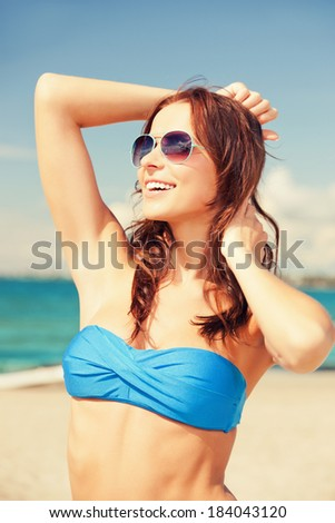 picture of happy woman in sunglasses on the beach - stock photo