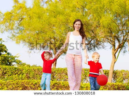 Picture of happy young family in park, cute pregnant mother with two sweet child walking outdoors in spring time, beautiful woman with son and daughter having fun on backyard, love and happiness - stock photo