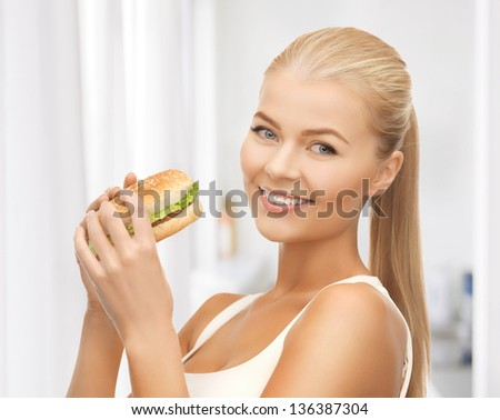 picture of healthy woman eating junk food - stock photo