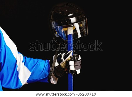 Picture of hockey helmet on hockey player stick - stock photo