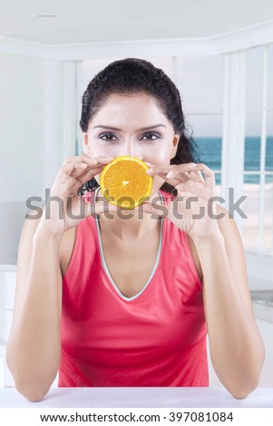 Picture of Indian healthy female model holding an orange slice while sitting in the kitchen - stock photo