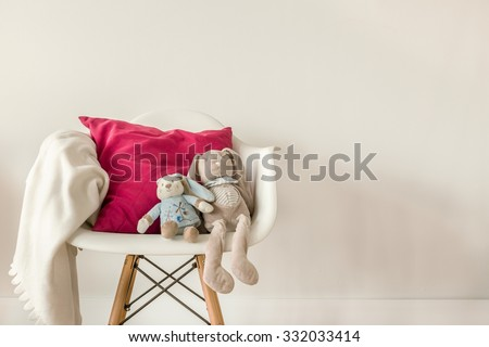 Picture of infant accessories on white modern chair - stock photo
