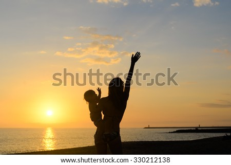 Picture of joyful young woman holding baby in sunset sunlights. Silhouette of happy family on dramatic seascape background.