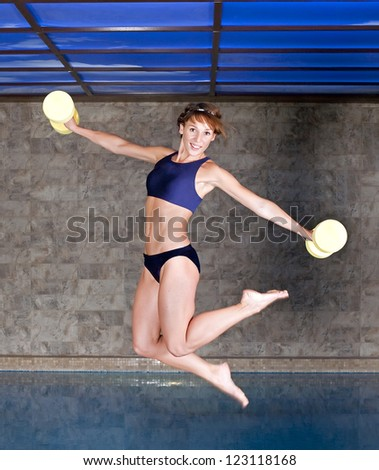 picture of jumping girl with water gear near the swimming pool - stock photo