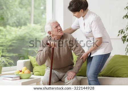 Picture of kind nurse helping elderly man to stand up - stock photo