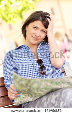 Picture of lost tourist with map sitting on a bench