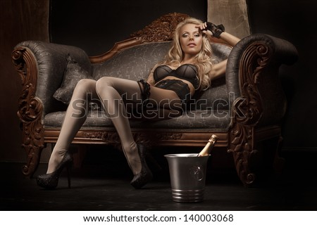 picture of lovely blonde in lingerie sitting on the sofa - stock photo